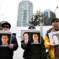 Protesters hold photos of Canadians Michael Spavor and Michael Kovrig, who are being detained by China, outside the British Columbia Supreme Court in Vancouver in March 2019. | AFP-JIJI