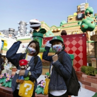Visitors pose in front of the newly opened Super Nintendo World at Universal Studios Japan in Osaka on Thursday. | KYODO