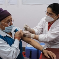 A health worker administers the Covishield vaccine, developed by AstraZeneca Plc. and the University of Oxford and manufactured by Serum Institute of India Ltd., in New Delhi on March 1. | BLOOMBERG