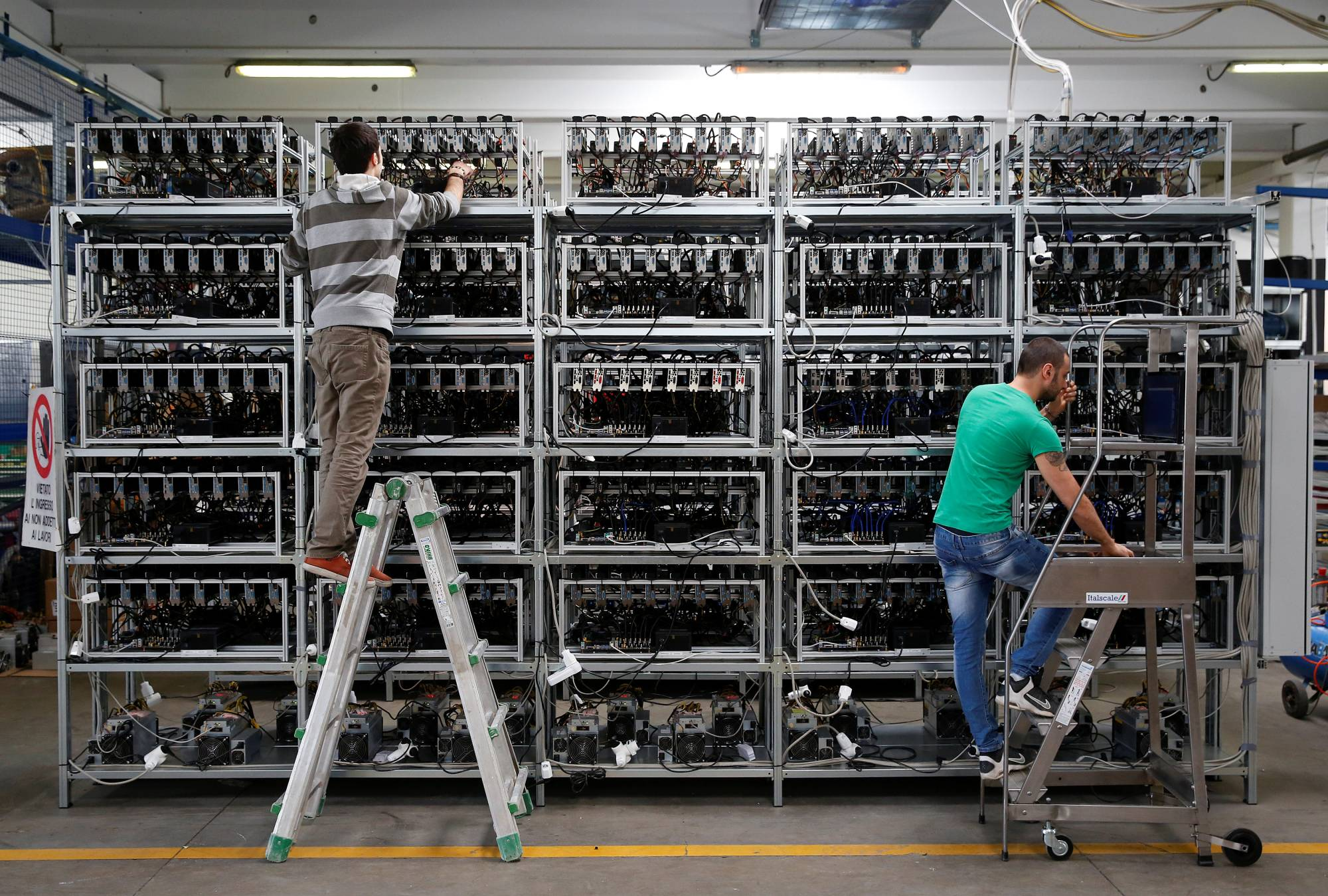 Employees work on bitcoin mining computers at Bitminer Factory in Florence, Italy, in April 2018. | REUTERS