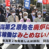 Plaintiffs hold a sign saying they oppose restarts at the Tokai No. 2 nuclear power plant as they head to a court ruling in Mito, Ibaraki Prefecture, on Thursday. | KYODO