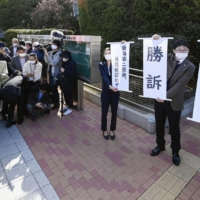 Lawyers for the plaintiffs hold banners reading 'victory' in their suit seeking the suspension of the Tokai No. 2 nuclear power plant, at Mito District Court in Ibaraki Prefecture on Thursday.