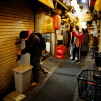 An employee of a Japanese restaurant closes his shop minutes after 8 p.m. in Tokyo on Jan. 8.   | REUTERS
