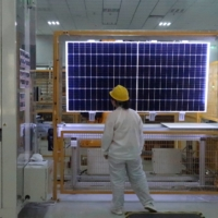 A worker conducts a quality-check of a solar module product at a factory in Xian, China. | REUTERS