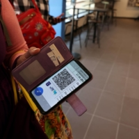 A woman shows her COVID-19 vaccination status on her mobile phone at a gym, where a 'green passport' is required to enter, in Tel Aviv in February. | REUTERS