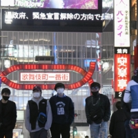 People walk in Tokyo's Kabukicho nightlife entertainment district on Wednesday. | KYODO