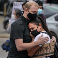 Demonstrators embrace during a rally Thursday calling attention to the rise in violence against Asian Americans, outside Gold Spa near Acworth, Georgia, one of three establishments targeted in a mass shooting earlier this week.  | CHANG W. LEE / THE NEW YORK TIMES