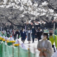 People walk in Ueno Park in Tokyo on Thursday. | KYODO