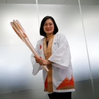Hiromi Kawamura, senior director of planning and international coordination for the Tokyo Olympic torch relay, holds the Tokyo 2020 torch during an interview in Tokyo on Friday. | REUTERS