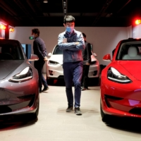 A man wearing a face mask walks by Tesla Model 3 sedans and a Tesla Model X sport utility vehicle at a showroom in Shanghai in May 2020.  | REUTERS