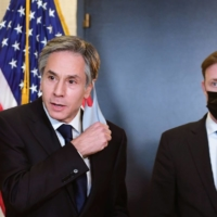 U.S. Secretary of State Antony Blinken takes off his mask before addressing the media beside national security adviser Jake Sullivan following closed-door morning talks between the United States and China upon conclusion of their two days of meetings in Anchorage, Alaska, on Friday. | POOL / VIA REUTERS