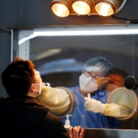 A man undergoes a coronavirus test at at a temporary site set up at Seoul's City Hall Plaza last December. | REUTERS