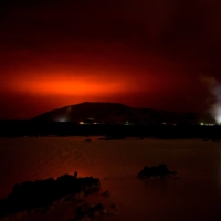 The red shimmer from magma flowing out from the erupting Fagradalsfjall volcano is seen behind the landmark Blue Lagoon, some 45 km west of the Icelandic capital of Reykjavik, on Friday. | AFP-JIJI