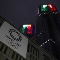 The Tokyo Metropolitan Government Office building is lit up with the Olympic colors last July. | REUTERS