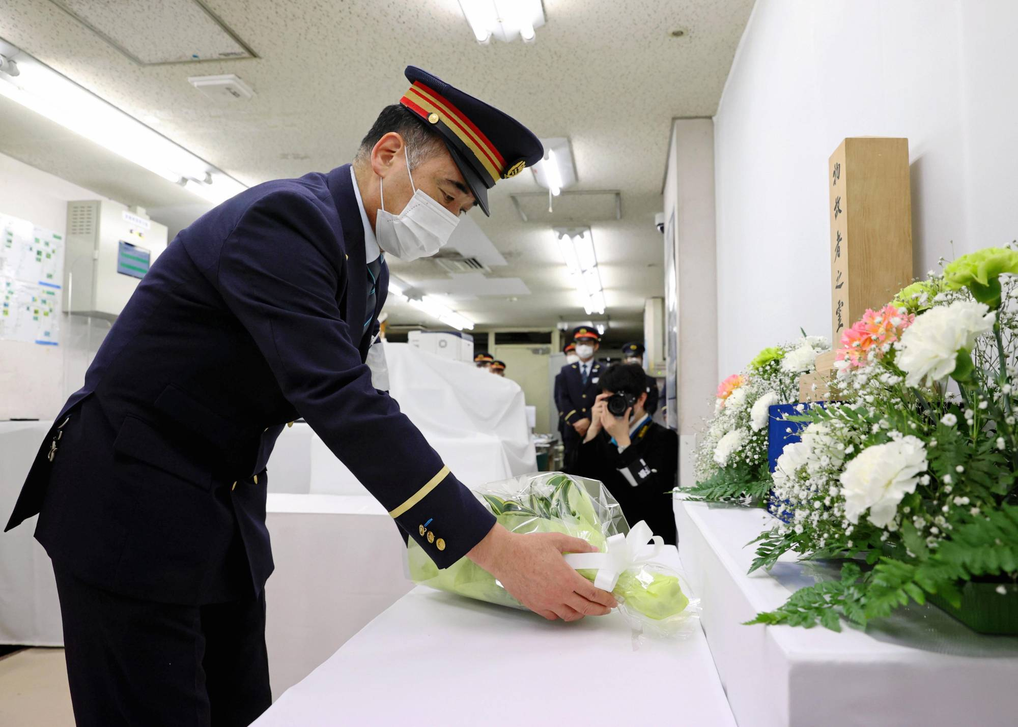 A Tokyo Metro employee offers flowers to the victims of the sarin nerve gas attack in Tokyo's subway system on Saturday, which marked the 26th anniversary of the killings.  | POOL / VIA KYODO