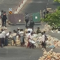 This photo taken and received courtesy of an anonymous source via Facebook on Saturday shows security forces watching as people remove a barricade across a road in the Yankin township of Yangon, amid a crackdown on demonstrations against the military coup. | AFP-JIJI