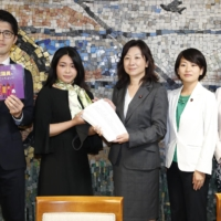 A civic group submits a petition to increase the number of female politicians to lawmakers at the Liberal Democratic Party's headquarters in Tokyo last October. | KYODO