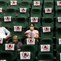 People sit under observation after receiving a dose of a vaccine in Ahmedabad, India, earlier this month.  | REUTERS