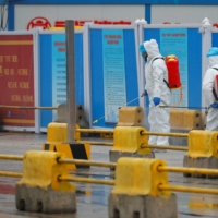 Workers spray the ground with disinfectant at Wuhan's Baishazhou market in January during the visit of a World Health Organization team tasked with investigating the origins of the COVID-19 pandemic. | REUTERS