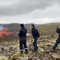 Icelandic Coast Guard staff inspect the lava flowing from the erupting Fagradalsfjall volcano on Saturday.  | ICELANDIC COAST GUARD / VIA AFP-JIJI