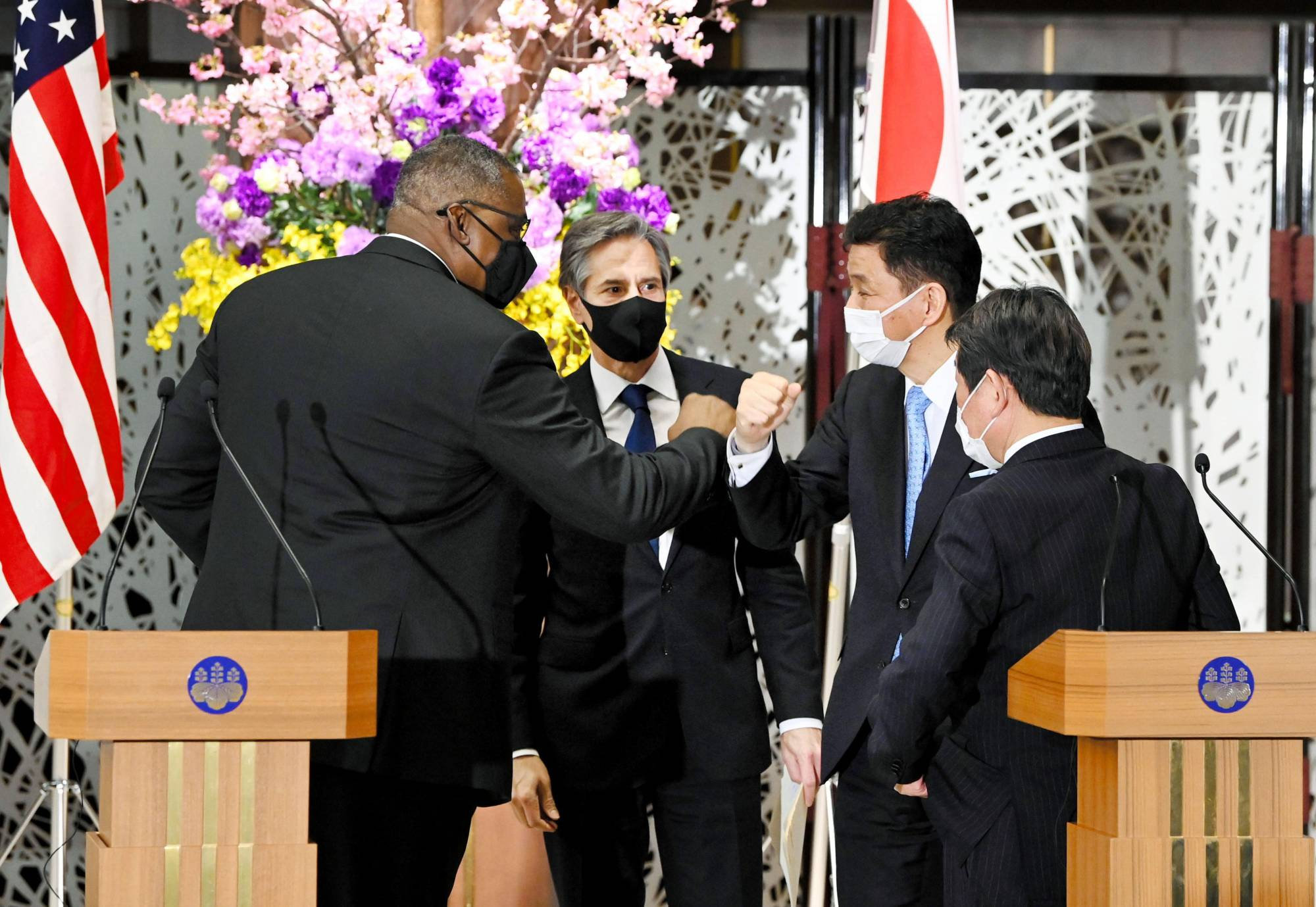 U.S. Defense Secretary Lloyd Austin (left) and Defense Minister Nobuo Kishi (second from right) do elbow bumps following a joint news conference in Tokyo on Tuesday.   POOL / VIA KYODO