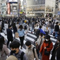 People walk in Tokyo's Shibuya district on Thursday. | KYODO