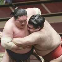 Takayasu (right) attacks Terunofuji during their Day 8 bout on Sunday at Ryogoku Kokugikan. | KYODO