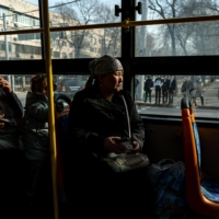 Gulnur Kosdaulet rides on a bus to the Chinese Consulate in Almaty to stage a protest against her husband's detention in China. | AFP-JIJI