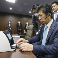 Health minister Norihisa Tamura tries out the new My Number and health insurance card system at the ministry in November. | KYODO