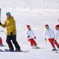 Former Olympian skier Sho Endo and children ski on a slope in Inawashiro in Fukushima Prefecture during a Tokyo Olympics torch relay rehearsal on March 15. | KYODO