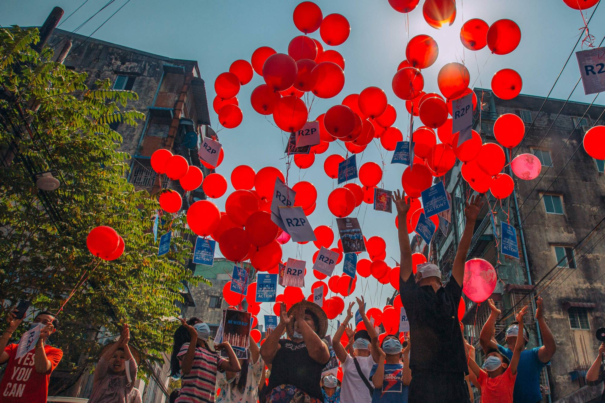 Residents release balloons on Monday bearing messages calling for international help following the coup in Myanmar, in Yangon's Hlaing township.  | FACEBOOK / VIA AFP-JIJI