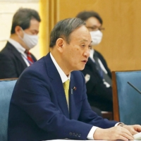 Prime Minister Yoshihide Suga speaks at a meeting of Cabinet ministers on additional spending for COVID-19 measures on Tuesday. | KYODO