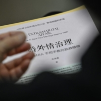 A woman holds a book about extramarital affairs as she listens to marriage counselor Zhu Shenyong during a session in Shanghai. | AFP-JIJI