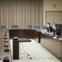 Industry minister Hiroshi Kajiyama (front right) and IAEA Director General Rafael Grossi hold talks during a videoconference Tuesday. | KYODO