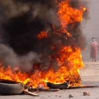 A woman walks near burning barricades during a crackdown by security forces on demonstrations by protesters against the military coup in Mandalay, Myanmar, in this photo taken and provided by anonymous source via Facebook. | AFP-JIJI