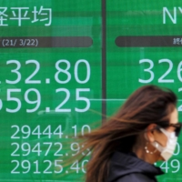 A pedestrian walks past an electronic quotation board displaying share prices of the Tokyo Stock Exchange in Tokyo on March 22. This year's and next year's growth numbers will speak for themselves, with Asia poised to pull away even further from a de facto stagnating Western world.  | AFP-JIJI
