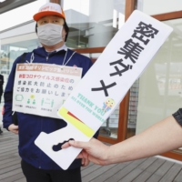 A member of staff hold signs calling on people to maintain social distance along the route of the Olympic torch relay in Naraha, Fukushima Prefecture, on Thursday. | KYODO