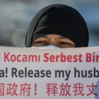 A member of Uyghur minority holds a placard during a demonstration near the Chinese Consulate in Istanbul on Feb. 22. | AFP-JIJI