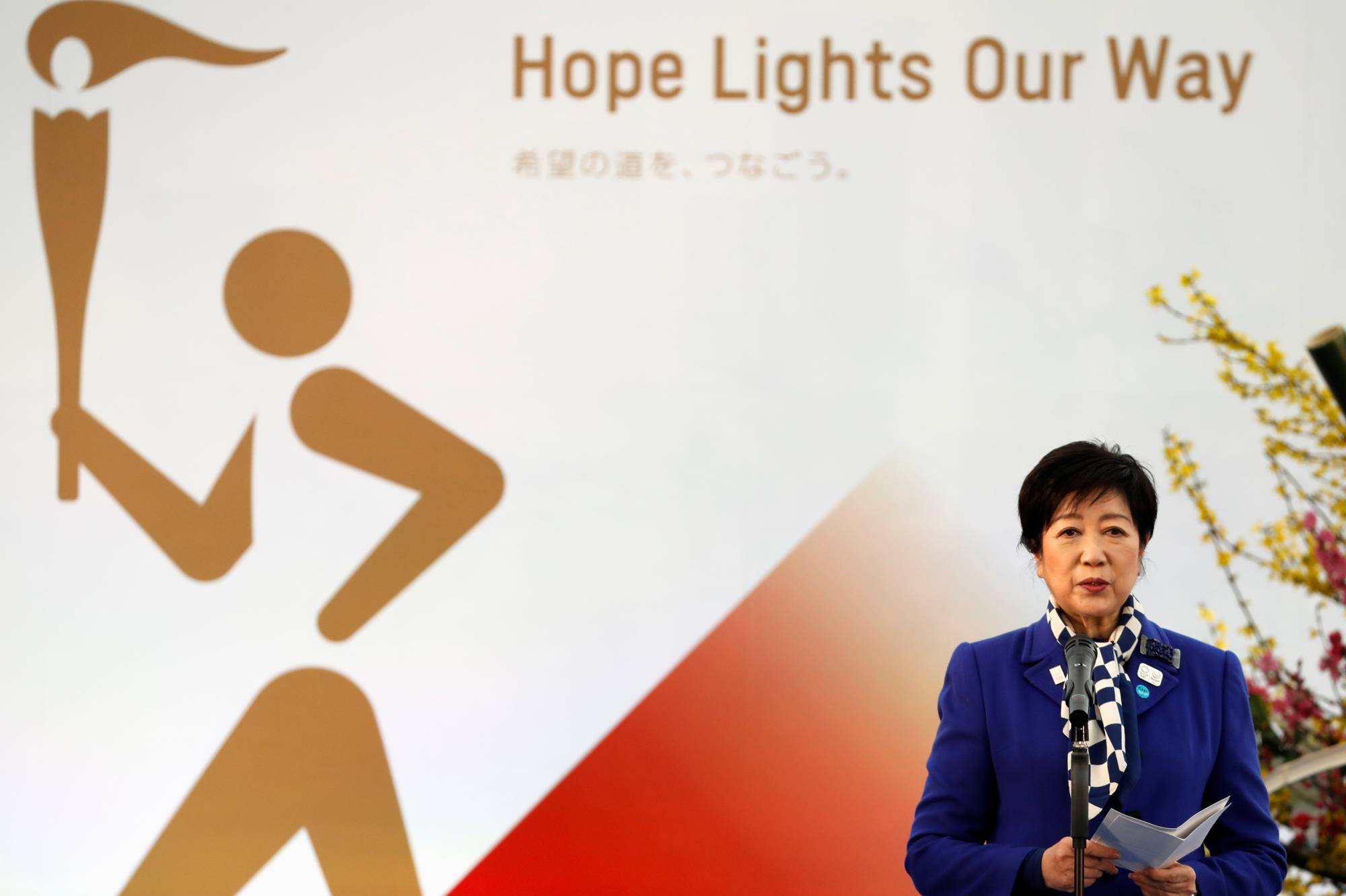 Tokyo Gov. Yuriko Koike delivers a speech at the start of the Olympic Torch Relay in Naraha, Fukushima Prefecture, on Thursday. | POOL / VIA REUTERS