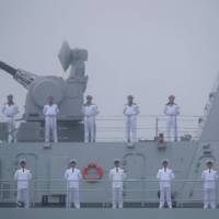 Chinese sailors stand on the deck of the guided missile destroyer Nanchang of the Chinese People's Liberation Army Navy on April 23, 2019. | POOL / VIA AFP-JIJI
