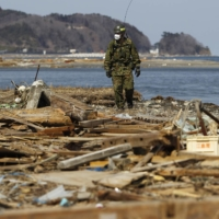 A member of the Self-Defense Forces searches for victims along a coastline that was damaged by the March 11, 2011, earthquake and tsunami, in Miyako, Iwate Prefecture, on April 5, 2011. | REUTERS