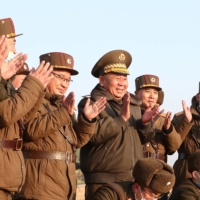 Ri Pyong Chol (center), the senior leader who oversaw the test, and other military officials applaud after the launch of a newly developed tactical guided projectile in North Korea on Thursday. | KCNA / VIA REUTERS