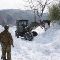 Self-Defense Forces personnel have been used for assistance and rescue operations in heavy snow in recent years, such as in Marumori, Miyagi Prefecture, in February 2014. | GROUND SELF-DEFENSE FORCE / VIA REUTERS