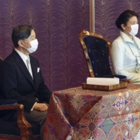 Emperor Naruhito (left) and Empress Masako attend a poetry reading ceremony held at the Imperial Palace on Friday. | POOL / VIA KYODO