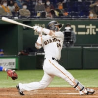 Giants catcher Takumi Oshiro connects on a three-run home run against the BayStars during the third inning at Tokyo Dome on Friday night.  | KYODO