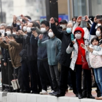 Spectators wearing face masks take photos and videos along the route of the Tokyo 2020 Olympic torch relay in the city of Fukushima on Friday. | REUTERS
