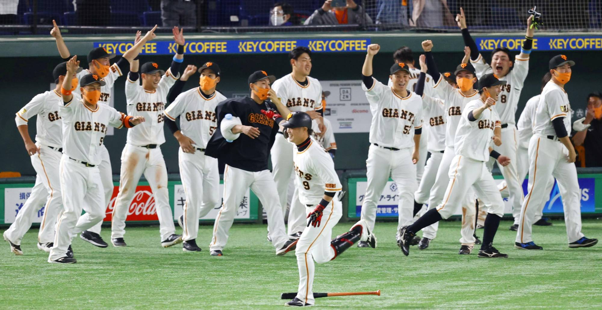 The Giants' Yoshiyuki Kamei begins to round the bases as his teammates celebrate after his walk-off home run on Friday at Tokyo Dome. | KYODO