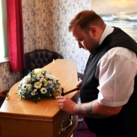 Funeral director Bobby Palliser prepares a coffin in Sheerness.  | REUTERS