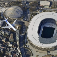 An airplane flies over the new National Stadium in Tokyo's Shinjuku Ward using a new flight route on March 23. | KYODO