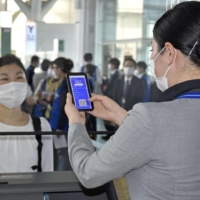 An All Nippon Airways Co. staff member (right) checks the CommonPass app indicating a traveler's COVID-19 status at Tokyo's Haneda Airport on Monday during a trial. | KYODO